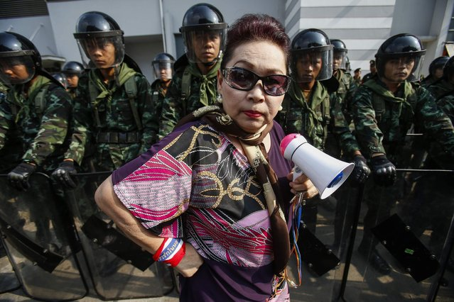 An anti-government protester stands near Thai soldiers guarding a Defence Ministry compound, which is serving as a temporary office for Thai Prime Minister Yingluck Shinawatra, in north Bangkok, on February 18, 2014. (Photo by Athit Perawongmetha/Reuters)