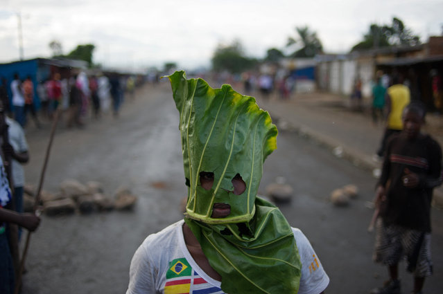 A protester wears a mask made from a leaf in the Cibitoke neighbourhood of Bujumbura on May 5, 2015. Protesters in Burundi dismissed a constitutional court ruling that cleared President Pierre Nkurunziza to run for a controversial third term, as the government offered to release activists if deadly demonstrations stopped. (Photo by Phil Moore/AFP Photo)