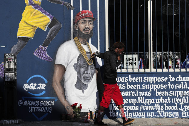 A man touches a mural depicting slain rapper Nipsey Hussle, Tuesday, April 2, 2019, in Los Angeles. Hussle was shot and killed Sunday, March 31, outside of his clothing store in Los Angeles. (Photo by Jae C. Hong/AP Photo)