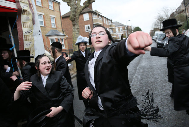 Members of the Jewish community dance in the street as they celebrate the festival of Purim in Stamford Hill in north London, Britain March 24, 2016. (Photo by Neil Hall/Reuters)