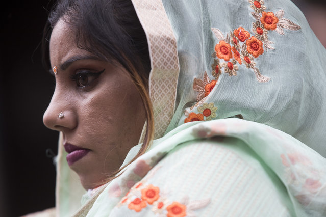 A Sikh woman watches as participants march down Madison Avenue during the Sikh Day Parade, celebrating the Sikh holiday of Vaisakhi, Saturday, April 27, 2019, in New York. (Photo by Mary Altaffer/AP Photo)