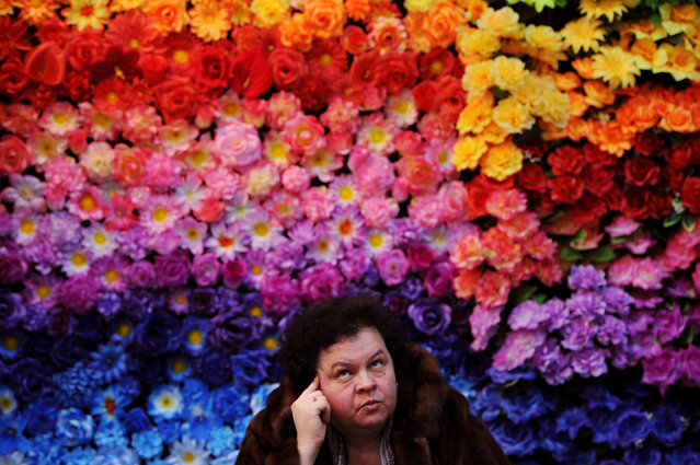 A woman sits in front of a wall of artificial flowers during the international Memorial and Stone Working fair in Minsk on February 15, 2017. (Photo by Sergei Gapon/AFP Photo)