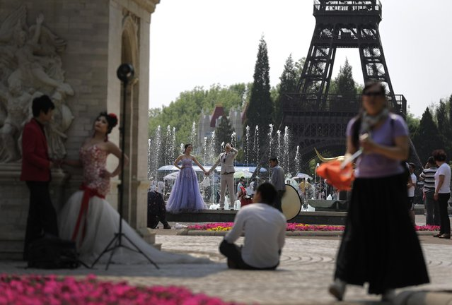 A groom reacts next to his bride as they pose for wedding photo against the replica of Eiffel Tower on display at the World Park in Beijing, China, Saturday, May 2, 2015. (Photo by Andy Wong/AP Photo)