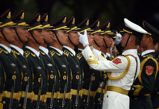 Chinese soldiers adjust their positioning before performing in an honour guard for India's Prime Minister Narendra Modi outside the Great Hall of the People in Beijing on May 15, 2015. Modi is on a three-day state visit to China. (Photo by Greg Baker/AFP Photo)
