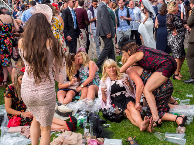Less than lady like behaviour on Ladies' Day at Epsom, England on June 2, 2017. Ladies' Day is traditionally held on the first Friday of June, a multitude of ladies and gents head to Epsom Downs Racecourse to experience a day full of high octane racing, music, glamour and fashion. (Photo by Peter Dench/Getty Images Reportage)