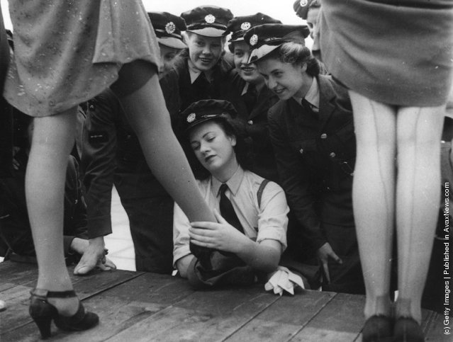 1943: Servicewomen look at a design of artificial silk-plated stocking, called 731, specially designed for servicewomen at a fashion show at Kennards of Croydon
