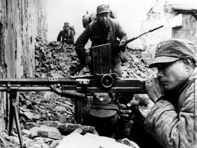 1944: A Chinese machine gunner takes aim in the ruins of a Chinese city