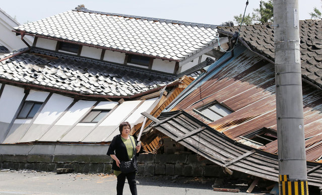 A woman walks past houses destroyed by Thursday's earthquake in Mashiki, Kumamoto prefecture, southern Japan, Friday, April 15, 2016. (Photo by Naoya Osato/Kyodo News via AP Photo)