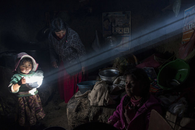 In this February 4, 2017 photo, a child holds a bowl of hot food as the Avila family has lunch at their home in Coata, a small village on the shore of Lake Titicaca in the Puno region of Peru. Lake Titicaca was once worshipped by Incas who proclaimed its deep blue waters the birthplace of the sun, but today high levels of mercury, cadmium, zinc and copper are found in the fish locals consume, according to a 2014 government study. (Photo by Rodrigo Abd/AP Photo)