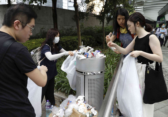 Protestors clean up trash near the Legislative Council in Hong Kong, Wednesday, June 12, 2019. Thousands of protesters blocked entry to Hong Kong's government headquarters Wednesday, delaying a legislative session on a proposed extradition bill that has heightened fears over greater Chinese control and erosion of civil liberties in the semiautonomous territory. (Photo by Vincent Yu/AP Photo)