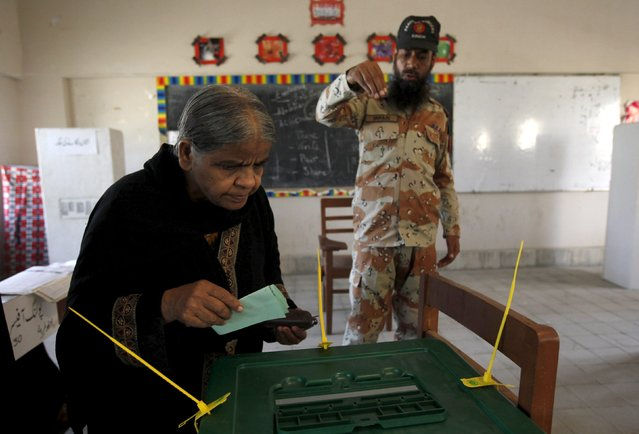 A Pakistan paramilitary personnel assists a voter during municipal by-elections in Karachi, Pakistan April 23, 2015. The chief of Pakistan's main spy agency is spearheading a campaign to wrest control of the teeming port city of Karachi from a powerful political party, the military's latest, and some say boldest, foray into civilian life in recent years. (Photo by Akhtar Soomro/Reuters)
