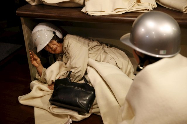 A woman takes shelter after another earthquake hit the area at a hotel in Kumamoto, southern Japan, in this photo taken by Kyodo April 16, 2016. (Photo by Reuters/Kyodo News)