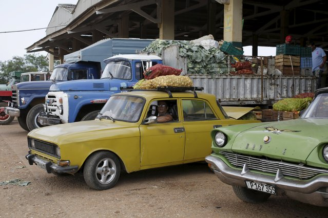 A man sits in a car loaded with onions and garlics at a wholesale market in Havana April 13, 2016. (Photo by Enrique de la Osa/Reuters)