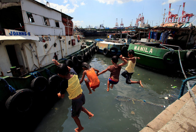 Children jump into the polluted waters of the Manila bay to cool off from the intense heat within the slum area of the Baseco compound in Tondo city, metro Manila, Philippines on April 30, 2018. (Photo by Romeo Ranoco/Reuters)
