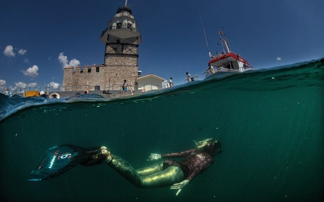 """A diver performs a special dive marking the Maritime and Cabotage Day in Istanbul, Turkey on June 27, 2019. The first emergency response ship of Turkey """"Nene Hatun"""" increases the operational strength of the Police General Directorate in ship accidents, marine pollution and fire with ships ability to operate in all kinds of weather conditions. Turkish freediver Bilge Cingigiray performed special dives at Maiden's Tower, Ortakoy and Heybeliada. The crew of the """"Nene Hatun"""" ship accompanied Cingigiray during her dive. Cingigiray and divers unfurled flags of Turkey and Directorate General of Coastal Safety. (Photo by Sebnem Coskun/Anadolu Agency/Getty Images)"""
