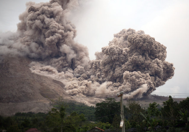 Mount Sinabung releases pyroclastic flows as seen from  Tiga Serangkai, North Sumatra, Indonesia, Saturday, June 13, 2015. The volcano, which was put on it highest alert level last week, has sporadically erupted since 2010 after being dormant for 400 years. (AP Photo/Binsar Bakkara)