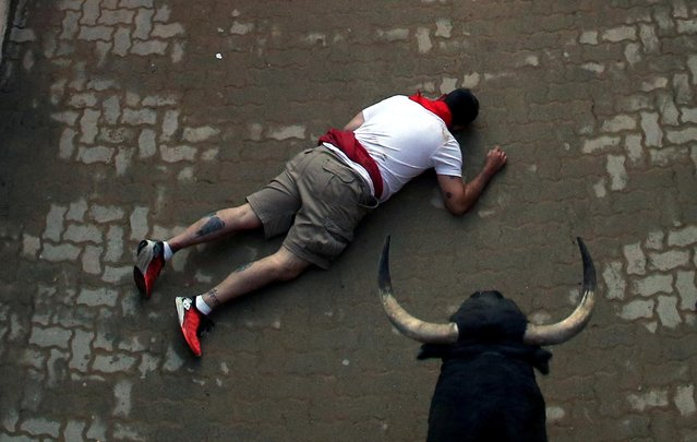 A reveller falls at the entrance of the bullring during the running of the bulls at the San Fermin festival in Pamplona, Spain, July 10, 2019. (Photo by Jon Nazca/Reuters)