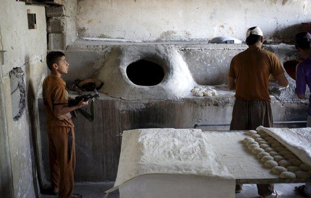 A Kurdish boy holds an AK-47 rifle in a bakery shop in Tuz Khurmato, Iraq, April 26, 2016. (Photo by Goran Tomasevic/Reuters)