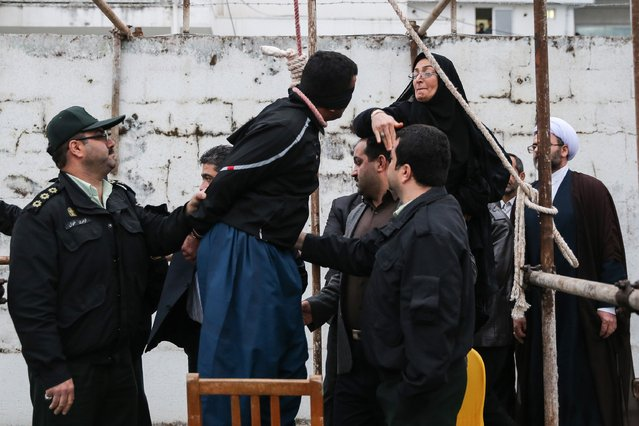 The mother (R) of Abdolah Hosseinzadeh, who was murdered in 2007, slaps Balal who killed her son during the execution ceremony in the northern city of Nowshahr on April 15, 2014 just before she removed the noose around his neck with the help of her husband, sparing the life of her son's convicted murderer. The dramatic events followed a rare public campaign to save the life of Balal, who at 19 killed another young man, Abdollah Hosseinzadeh, in a street fight with a knife back in 2007. (Photo by Araash Khamooshi/AFP Photo/ISNA)