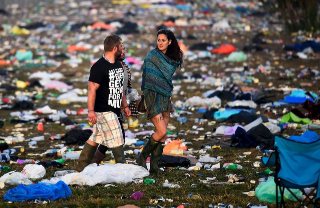Revellers walk through rubbish left in front of the Pyramid Stage as they leave Worthy Farm in Somerset after the Glastonbury Festival in Britain June 29, 2015. (Photo by Dylan Martinez/Reuters)