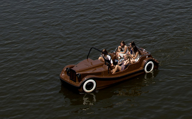 Tourists enjoy a sunny day as they cruise Vltava river in a pedal boat near the famous Charles bridge in Prague, Czech Republic on June 30, 2015. A recent heat is spreading across parts of Europe. (Photo by Joe Klamar/AFP Photo)