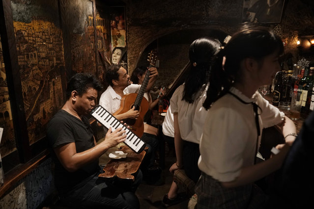 In this Sunday, July 28, 2019, photo, two musicians entertain patrons in a tiny bar at the Golden Gai in the Shinjuku district of Tokyo. (Photo by Jae C. Hong/AP Photo)