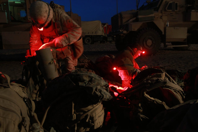 U.S. Marines from 3rd Battalion, 6th Marine Regiment read and pack their gear under red light head lamps at a forward operating campsite in Marjah in Afghanistan's Helmand province on Thursday February 18, 2010. (Photo by David Guttenfelder/AP Photo)