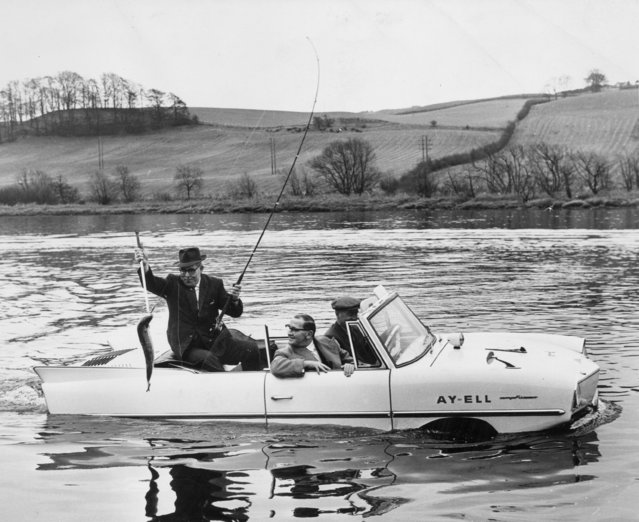 "On the day after the official opening of the Tay Salmon Rod Fishing Season, Duncan McGregor catches an 8lb salmon from Ian Cameron's amphibious car ""Ay-Ell"". United Kingdom, 16th January 1964. (Photo by Central Press/Getty Images)"