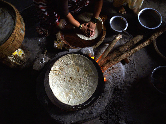 A fisherwoman prepares a meal in her home in a fishing village in Virar, about 40 km (25 miles) from Mumbai December 27, 2005. (Photo by Adeel Halim/Reuters)