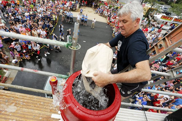 Ludovicus Poisson of a Belgian team from Antwerp empties buckets of water in the bucket brigade competition of the Firefighter Muster event at the World Fire and Police Games in Fairfax, Virginia July 4, 2015. (Photo by Jonathan Ernst/Reuters)