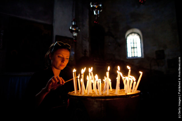 A woman lights candles as she prays in the Church
