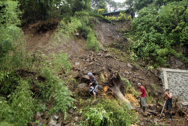 Government workers clear a portion of Kennon Road after heavy rains brought by tropical storm Linfa caused landslides in Tuba, Benguet, in northern Philippines July 6, 2015. (Photo by Harley Palangchiao/Reuters)