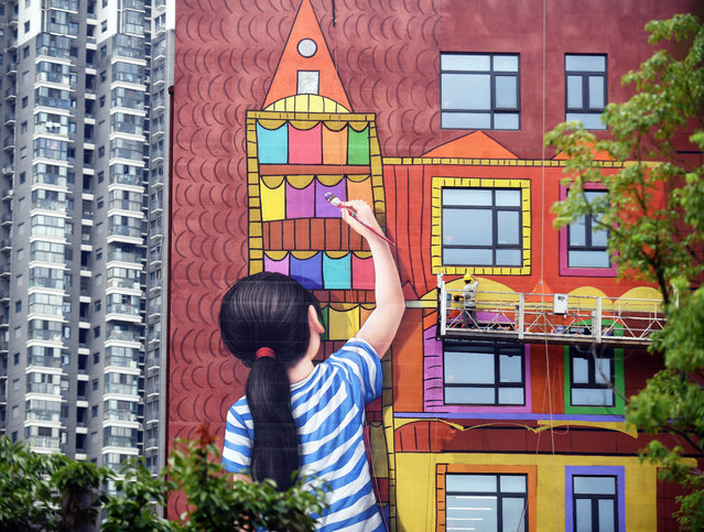 """A worker paints on the wall of Jiangsu Women and Children Health Hospital on September 4, 2019 in Nanjing, Jiangsu Province of China. The wall painting of """"a girl drawing colorful houses"""" is a part of Jiangsu Women and Children Health Hospital's """"Angel Plan"""" which hopes to heal people's soul with arts. (Photo by VCG/VCG via Getty Images)"""