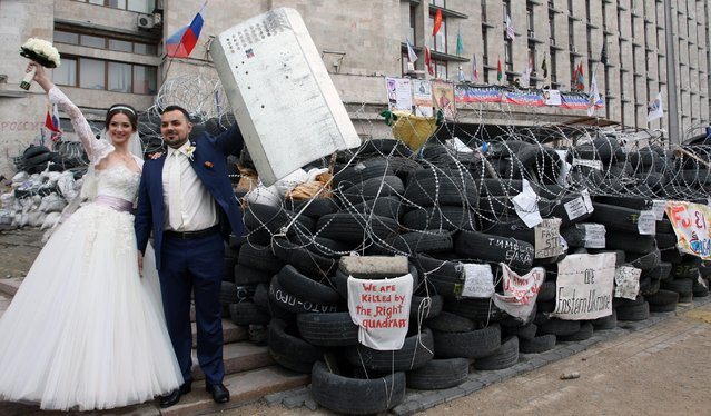 A couple on their wedding day poses at the barricades in the center of Donetsk in downtown of Donetsk, Ukraine, 02 May 2014. Injuries were reported the previous day after separatist forces swept aside security forces and stormed a government building, this time in the disputed eastern Ukrainian city of Donetsk. (Photo by Igor Kovalenko/EPA)