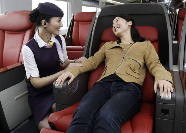 A train attendant helps a passenger to adjust her seat at the business class carriage on a CRH 380A bullet train  Thursday, June 16, 2011. (Photo by Reuters/China Daily)