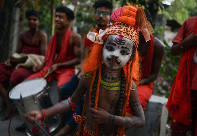 """An Indian child dressed as the Hindu deity Shiva dances with others as they begs for alms in Siliguri on April 12, 2017, ahead of the """"Charak"""" ritual that is observed on the last day of the Bengali calender year. Hindu devotees offer various symbolic sacrifices hoping for the favour of Shiva to mark the advent of the Bengali new year, which falls on April 14. (Photo by Diptendu Dutta/AFP Photo)"""