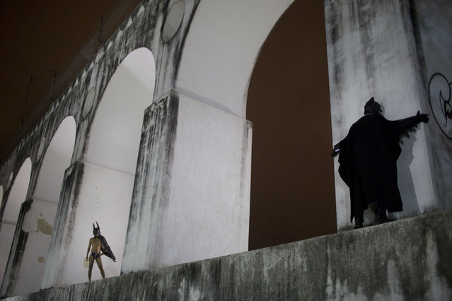 "Protesters wearing Batman costumes stand over the Carioca Aqueduct, also know as Arcos da Lapa, during a demonstration in Rio de Janeiro, Brazil, Thursday, October 31, 2013. People demonstrated against the government, police violence, corruption, the recent arrest of protesters and several other issues. Organisers called the march ""the freedom shout"". (Photo by Felipe Dana/AP Photo)"