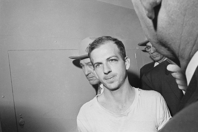Lee Harvey Oswald is led down a corridor of the Dallas police station for another round of questioning in connection with the assassination of President John F. Kennedy, November 23, 1963. Oswald, who denies any involvement in the shooting, is formally charged with murder. (Photo by AP Photo)