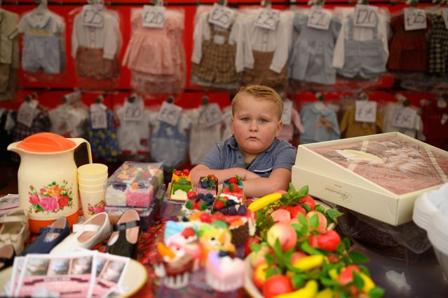 A boy staffs a clothing and household goods stall at the biannual Stow Horse Fair in the town of Stow-on-the-Wold, southern England on October 24, 2019. (Photo by Oli Scarff/AFP Photo)