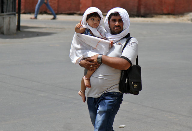 A man and a child cover up from the sun in the city of Ajmer, India May 23, 2016. (Photo by Himanshu Sharma/Reuters)