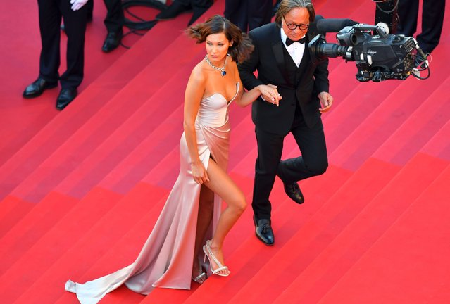 """US model Bella Hadid (L) and her father Mohamed Hadid arrive on May 17, 2017 for the screening of the film """"Ismael's Ghosts"""" (Les Fantomes d'Ismael) during the opening ceremony of the 70th edition of the Cannes Film Festival in Cannes, southern France. (Photo by Loic Venance/AFP Photo)"""