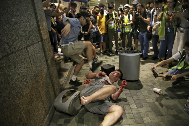 A man hits a suspected attacker after an incident broke out outside a Hong Kong mall, on Sunday, November 3, 2019. Riot police stormed several malls in Hong Kong on Sunday in a move to thwart more pro-democracy protests, though violence did break out when the knife-wielding man slashed several people and bit off part of the ear of a local pro-democracy politician. (Photo by Elson Li/HK01 via AP Photo)