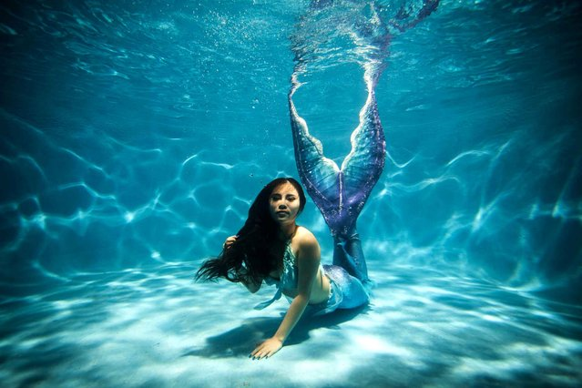 This photo taken on July 26, 2015 shows a woman clad in her self-made mermaid costume swimming in a pool in China's southwest Chongqing municipality. (Photo by AFP Photo/Stringer)
