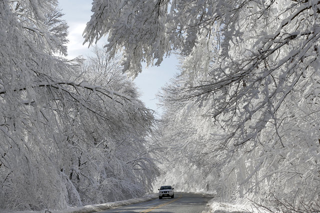 A car makes its way through a snowy landscape in Highland Falls, N.J., Tuesday, December 3, 2019. The last of the snow is falling over parts of New Jersey after leaving behind power outages in the northwest part of the state. (Photo by Seth Wenig/AP Photo)