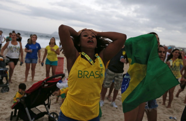 A Brazilian soccer fan reacts as she watches the opening match of the 2014 World Cup between Brazil and Croatia at the Copacabana beach in Rio de Janeiro June 12, 2014. (Photo by Pilar Olivares/Reuters)