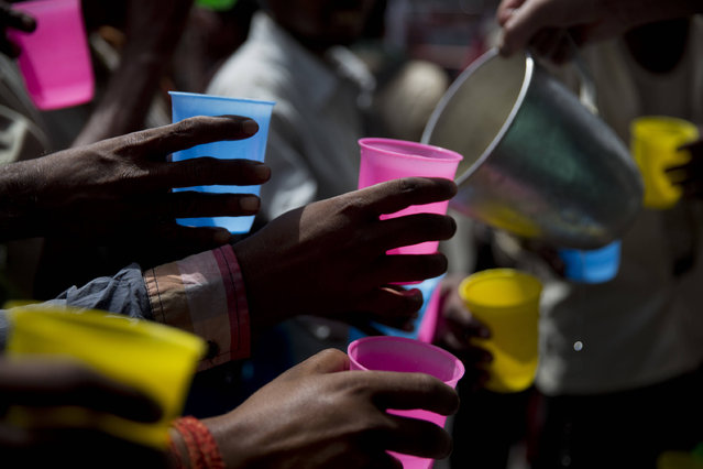 Indians reach to get a cold drink being freely distributed by a roadside on hot summer day in New Delhi, India, Monday, June 5, 2017. Most parts of northern India is reeling under intense heat wave conditions with the temperature crossing over 43 degrees Celsius (109.4 Fahrenheit). (Photo by Tsering Topgyal/AP Photo)