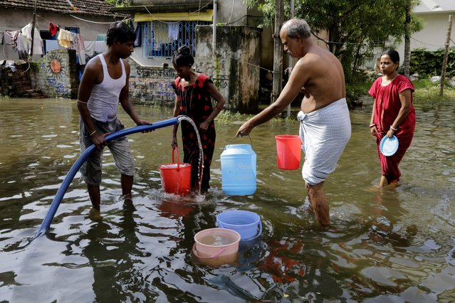 A civic worker distributes drinking water to residents surrounded by flood water at Mukundapur village near  Kolkata, West Bengal state, India, Monday, August 3, 2015. (Photo by Bikas Das/AP Photo)