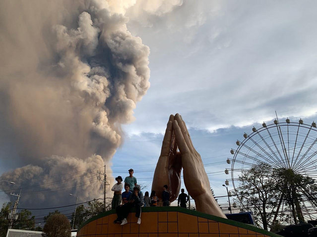 People watch as the Taal volcano spews ash and smoke during an eruption in Tagaytay, Cavite province south of Manila, Philippines on Sunday. January 12, 2020. A tiny volcano near the Philippine capital that draws many tourists for its picturesque setting in a lake belched steam, ash and rocks in a huge plume Sunday, prompting thousands of residents to flee and officials to temporarily suspend flights. (Photo by Bullit Marquez/AP Photo)