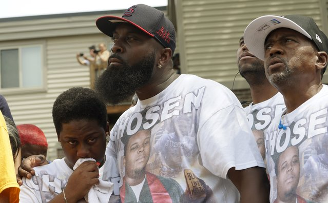 Michael Brown Sr., at the spot where his son was killed, comforts his wife Cal Brown during the 4-1/2 minutes of silence to mark the one-year anniversary of the killing of his son Michael Brown in Ferguson, Missouri August 9, 2015. (Photo by Rick Wilking/Reuters)