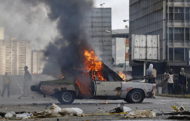 A car is engulfed in flames, set on fire by anti-government demonstrations during clashes with National Guards in Caracas, Venezuela, Thursday, July 20, 2017. (Photo by Ariana Cubillos/AP Photo)